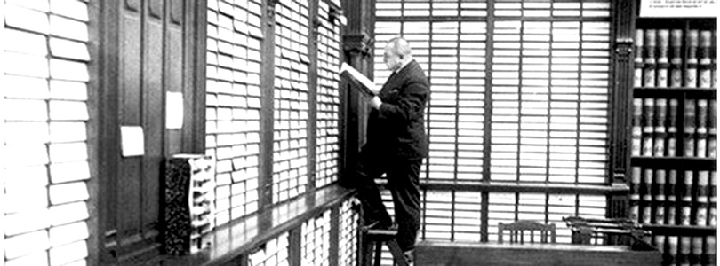 Historical picture of an examiner standing on a ladder in the Reichspatentamt library