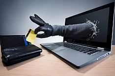 Black hand comes out of laptop and reaches into wallet