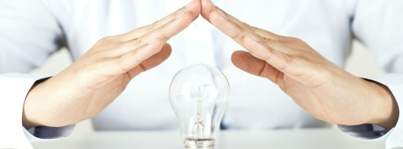 Two hands sheltering a light bulb